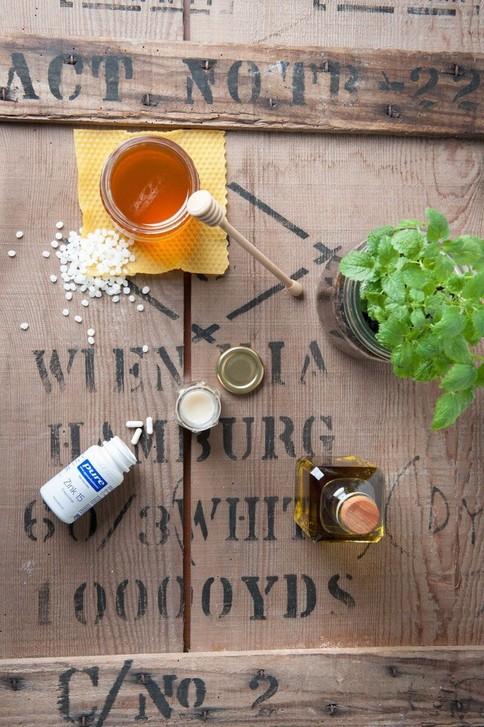 Für den Lippenbalsam benötigt man Honig, Bienenwachs, Olivenöl, ätherisches Melissen und 1 Pure Kapsel Zink Reinsubstanz.