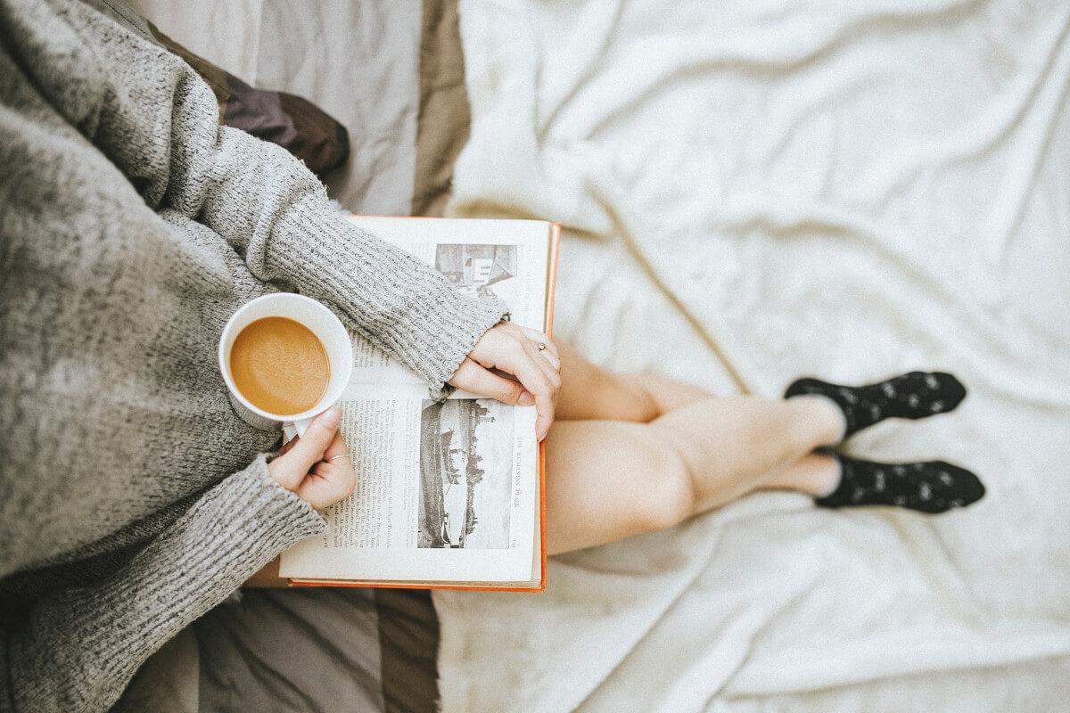Frau liegt im Bett, liest ein Buch und trinkt Kaffee.