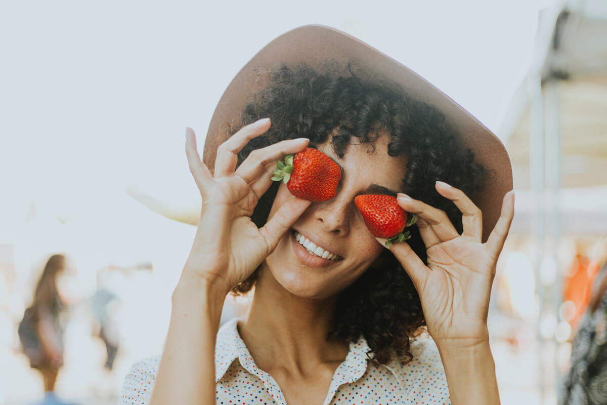 Frau mit Hut und Erdbeeren