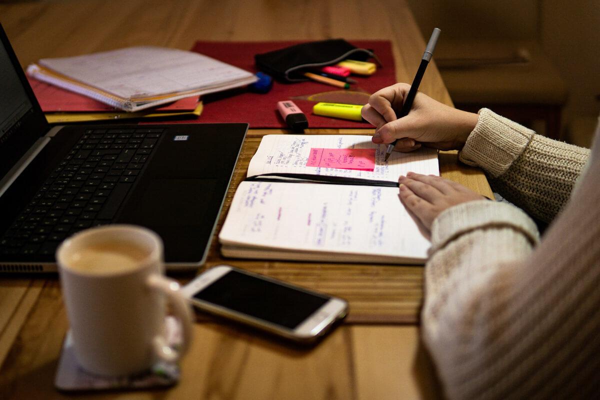 Arbeiten am Laptop mit Notizbuch, Handy und Kaffee