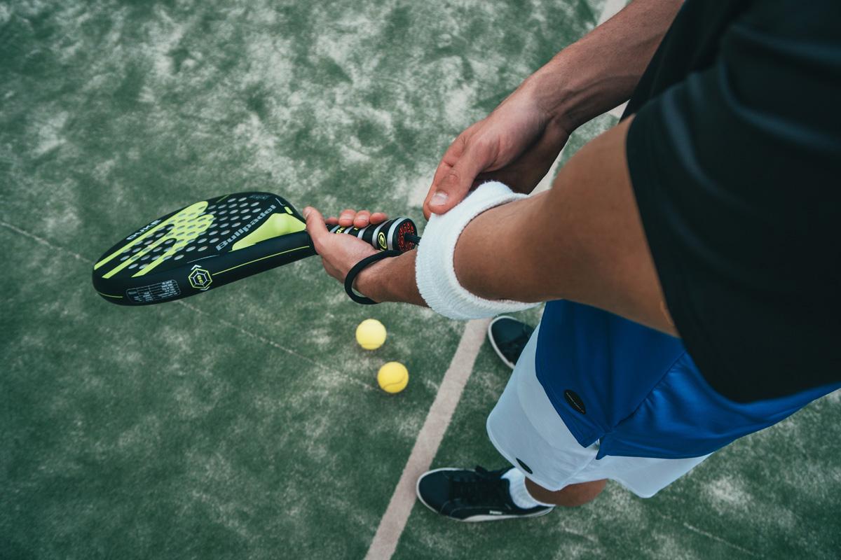 Muskelkater - oder die Tage danach. Mann hält Tennisschläger.