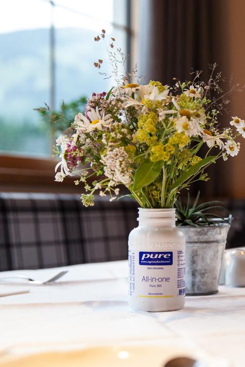 Leere Pure-Fläschchen lassen sich super als Blumen-Vase recyceln