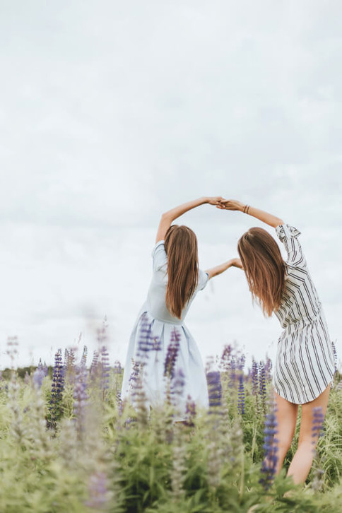 Zwei Mädchen stehen auf einer Blumenwiese und halten sich an den Händen.