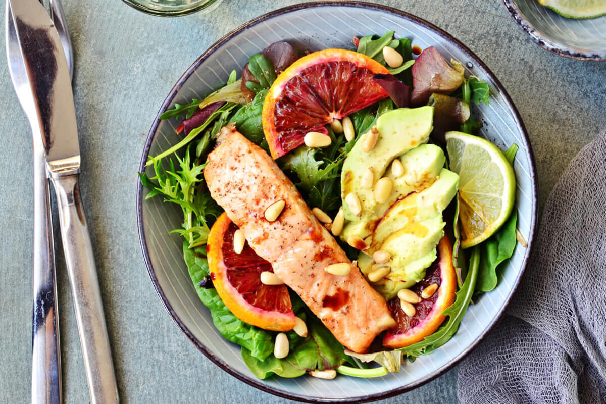 EIn Fischgericht mit Salat, Avocado und Blutorange