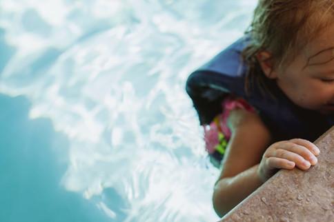 Kind lernt schwimmen im Schwimmbecken