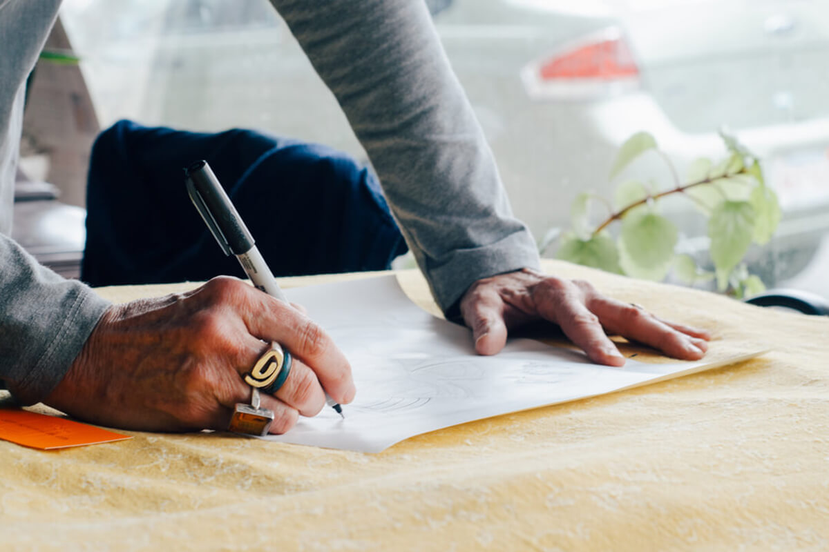 Eine ältere Dame zeichnet auf einem Blatt Papier.